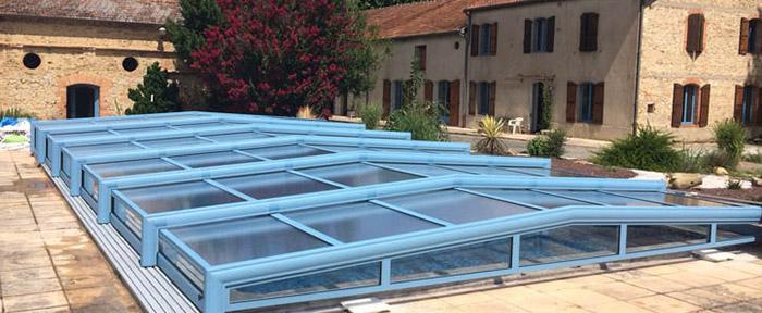 abri bas de piscine en verre avec une structure alu bleue
