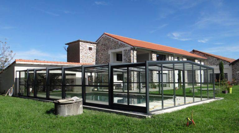 abri de piscine en verre par DCLS pour une maison traditionnelle en pierre