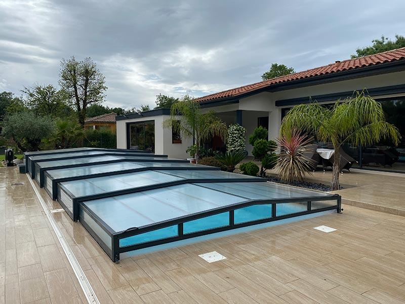 terrasse avec piscine recouverte d'un abri bas en verre cintré