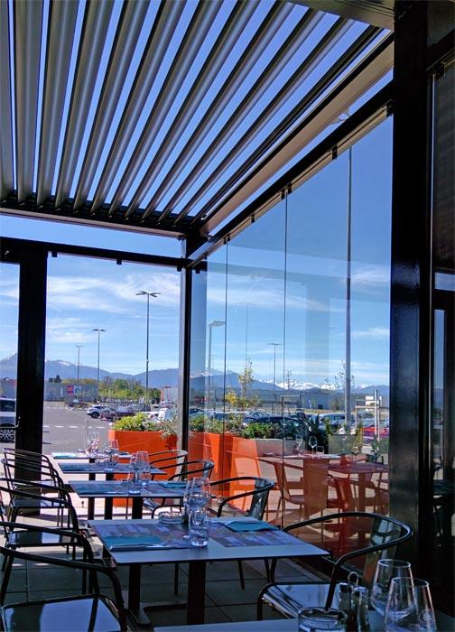 pergola bioclimatique à lames orientables pour restaurant avec parois de verre
