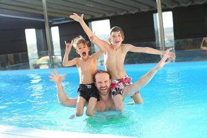 famille jouant dans la piscine, sous l'abri adossé