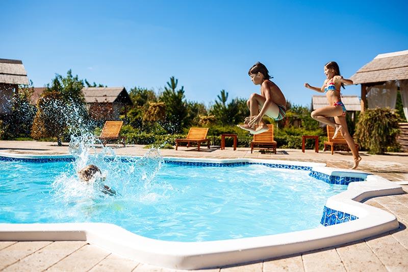 enfants qui sautent dans une piscine de camping